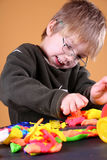 Young Artist. Young cute boy playing with plasticine royalty free stock photography