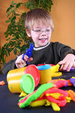 Young Artist. Young cute boy playing with plasticine royalty free stock image