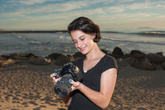 Young artist amused by her photos. Female teen photographer close view checking camera photos stock image