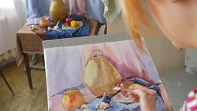 A young artist in an art workshop draws a still-life from nature in watercolor. stock video footage