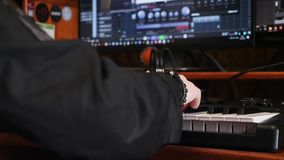 Young artist composing a song on electronic piano keyboard at home recording studio. Hand playing on piano in music studio. Sound. Engineer working on producing stock video footage