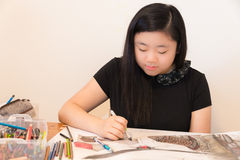 Young Artist Drawing. Beautiful Asian American female teen sitting at her table drawing. Horizontal. Copy space Stock Photo