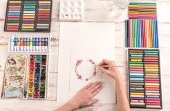 Young artist drawing pattern with watercolor paint and brush. Young artist drawing flowers pattern with watercolor paint and brush at workplace. Artist equipment Royalty Free Stock Photos