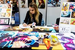 Young artist drawing manga posters. At the East European Comic Con in Bucharest, Romania, Romexpo 2017 royalty free stock image