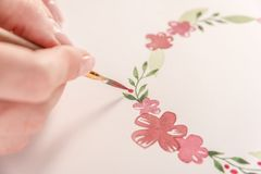Young artist drawing pattern with watercolor paint and brush. Close up of young artist drawing flowers pattern with watercolor paint and brush on paper at Royalty Free Stock Image