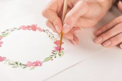 Young artist drawing pattern with watercolor paint and brush. Close up of young artist drawing flowers pattern with watercolor paint and brush on paper at Stock Image