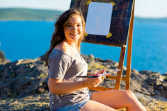 Young artist draws a seascape at sunset Stock Images
