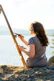 Young artist draws a seascape at sunset Royalty Free Stock Images