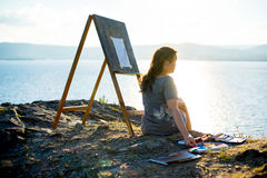 Young artist draws a seascape at sunset. On the highrock Stock Photography