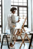 Young artist feeling truly inspired standing near drawing easel stock photo