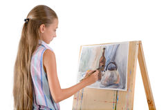 The young artist. The young girl draws on an easel Royalty Free Stock Image