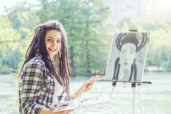 Young artist girl painting a self portrait in a park near lake - Painter woman with dreadlocks hairstyle working on her art stock photos