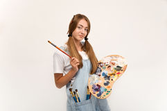 Young artist holding a brush to paint and palette. Royalty Free Stock Photography