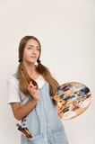 Young artist holding a brush to paint and palette. Royalty Free Stock Images