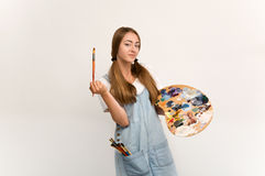 Young artist holding a brush to paint and palette. Royalty Free Stock Image