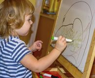 Little girl draws on the Board with colored markers. Young artist. Little girl draws on the Board with colored markers Royalty Free Stock Image
