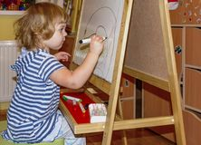 Little girl draws on the Board with colored markers. Young artist. Little girl draws on the Board with colored markers Stock Photography