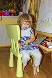 Little girl draws on the Board with colored markers. Young artist. Little girl draws on the Board with colored markers Royalty Free Stock Images