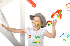 Young artist. The little girl, stained in colors with a brush in his hand Stock Photos
