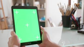 Young artist looks at a tablets green screen in his studio. Male hands hold a black tablet with green screen on stock video footage