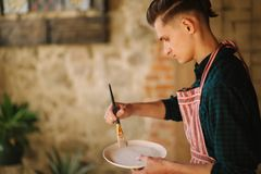 Young artist making ornament on ceramic plate. Handsome young man working at his workshop.  royalty free stock photos