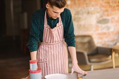 Young artist making ornament on ceramic plate. Handsome young man working at his workshop.  royalty free stock images