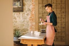 Young artist making ornament on ceramic plate. Handsome young man working at his workshop.  royalty free stock photography