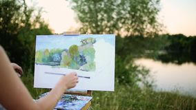 Young artist painting picture in park with brushes and colors sitting by the romantic lake and urban buildings in stock footage