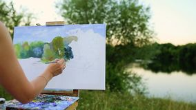 Young artist painting picture in park with brushes and colors sitting by the romantic lake and urban buildings in stock video footage