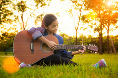 Young artist play solo guitar in green nature park Royalty Free Stock Photo