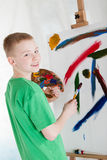 Young artist smiles over his shoulder near easel Stock Photo