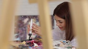 Artist squeezes the paint from the tube on palette. The young artist squeezes the oil paint from the tube on the palette, in the foreground blurred easel stock video