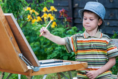 Young artist starting his work. Preschool boy painting flowers outdoor Stock Photography