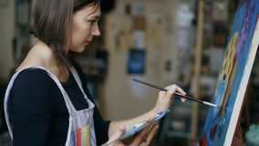 Young artist woman painting still life picture on canvas in art-school. Indoors stock video footage
