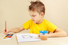 Young artist in yellow shirt painting with watercolors Royalty Free Stock Photos
