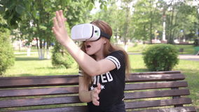 Young artistic blonde woman playing game using VR-helmet for smartphones. Modern augmented reality device. stock video