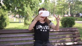 Young artistic blonde woman playing game using VR-helmet for smartphones. Modern augmented reality device. stock video footage