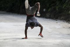 Man doing handstand and walking on street, Jamaica. Young artistic man doing hand stand, Ocho Rios, Jamaica stock image