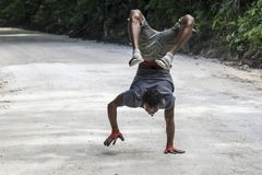 Man doing handstand and walking on street, Jamaican. Young artistic man doing hand stand, Ocho Rios, Jamaica stock photos