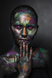 Young artistic woman in black paint and colourful powder. Glowing dark makeup. Creative body art on the theme of space. And stars. Bodypainting project: art stock photography