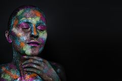 Young artistic woman in black paint and colourful powder. Glowing dark makeup. Creative body art on the theme of space. And stars. Bodypainting project: art Royalty Free Stock Image