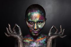 Young artistic woman in black paint and colourful powder. Glowing dark makeup. Creative body art on the theme of space. And stars. Bodypainting project: art stock photos
