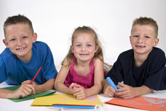 Young Artists. Three siblings lying on the floor coloring on bright colored paper Stock Photos