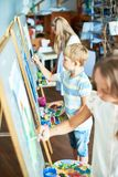 Young Artists in Art Studio. High angle portrait of three children painting on easels during art class in sunlit studio, focus on talented little boy in the royalty free stock image