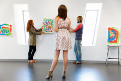 Young artists in gallery hanging painting on walls Stock Photo