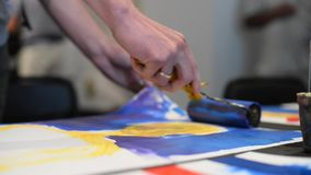 Young artists paint the details on picture while the performance in gallery Mistetskiy Arsenal stock footage