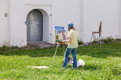 Young artists paint at the walls of an ancient cathedral Stock Images