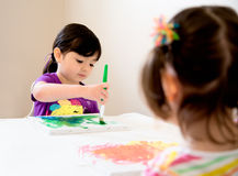 Young artists painting. Young girl painting a picture as her sister watches Royalty Free Stock Images