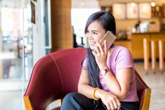 Young asain woman smiling in cafee shop talking mobile phone and texting in social networks. Sitting alone Stock Photo