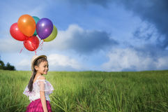 Young asia girl holds tightly to a large bunch of helium filled Royalty Free Stock Photos